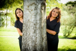 Two Crossroads Dental team members each picking from behind a different side of a big tree on the lawn in front of the dental office