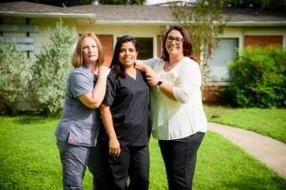 Three Crossroads Dental team members together posing for the photo on the lawn in front of the dental office