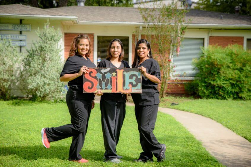 Three Crossroads Dental team members holding a sign: SMILE on the lawn in front of the dental office