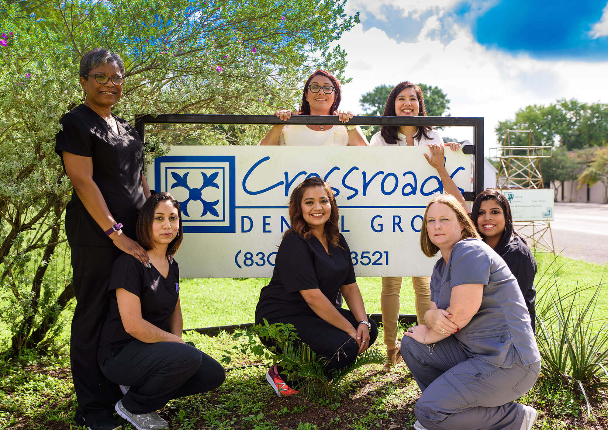 The team members of Crossroads Dental posing for a photo around the big sign on the front lawn